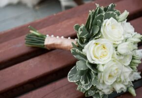 the-bride-s-beautifully-decorated-bouquet-of-white-roses-and-green-leaves-lies-on-a-brown-wooden-bench--wedding-theme--1153011819-7eb01a5a6fb74d2f81665b4f56371334